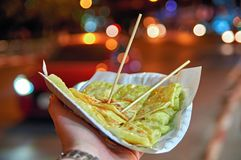 Asian street food concept, fastfood. Sweet pancake stuffed with banana and condensed milk. Wooden chopsticks. Night time. royalty free stock photos