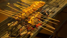 Asian street Food. People cooking, selling and buying Exotic Asi. Asian street Food, meat. People cooking, selling and buying Exotic Asian Food Thai, Malaysian Stock Photo