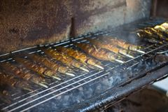 Asian street Food. People cooking, selling and buying fish Royalty Free Stock Photography