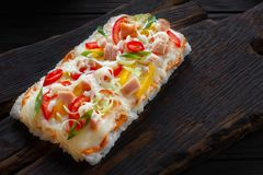 Asian street food. Tasty appetizing japanese rice pizza with bac. On served on rustic wooden table Royalty Free Stock Photography