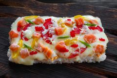 Asian street food. Tasty appetizing japanese rice pizza with sal. Mon served on rustic wooden table Royalty Free Stock Photos