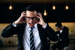 Stress business man in trouble. Asian stress business men having terrible headache and scream furiously while another men closing his face by hand and smartphone Stock Image