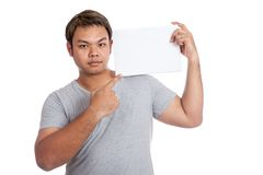 Asian strong man  flexing biceps point at  blank sign on shoulde Royalty Free Stock Photos