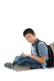 Asian student boy sitting and writing something. On white background Stock Photography