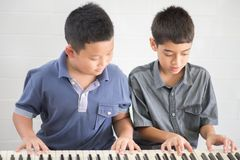 Asian student boys playing piano together in class royalty free stock images