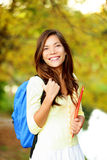Asian student girl back to school university. Beautiful woman holding books in autumn background. Asian student girl on university college campus park smiling Stock Images
