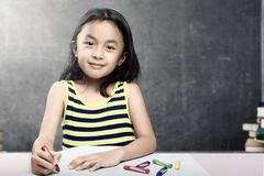 Asian student girl drawing on white paper with colorful crayons in the classroom with piles of books and blackboard background royalty free stock images