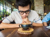 Asian student glasses man with cup of latte coffee. In art cafe Stock Photography