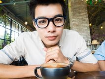 Asian student glasses man with cup of latte coffee. In art cafe Royalty Free Stock Photo