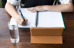 Asian student hand with pen writing on notebook. With glass of water on the table Stock Images