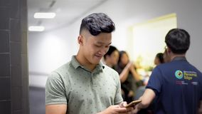 Asian handsome guy smile while using smartphone stock footage