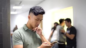 Asian handsome guy trying new app on smartphone with serious face stock footage