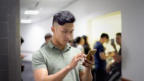 Asian handsome guy trying new app on smartphone with serious face stock video footage