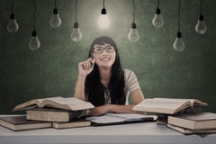 Asian student has bright idea under light bulbs Royalty Free Stock Images