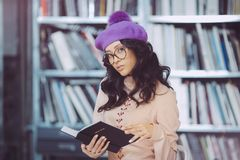 Asian student holding book in the library Royalty Free Stock Photos
