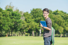 Asian student holding books and smiling while standing in park a royalty free stock photo