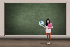 Asian student holding globe in class stock images