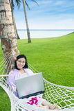 Asian student with laptop on hammock at beach Royalty Free Stock Photography