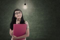 Asian student looking at lit bulb in class Royalty Free Stock Photos