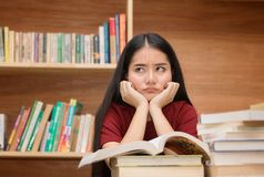 Asian student looking stressed while reading book preparing exam. Student looking stressed while reading book preparing examination in library Royalty Free Stock Photography