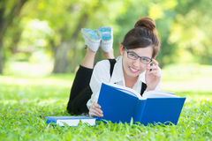 Asian student lying on grass reading book Royalty Free Stock Photos