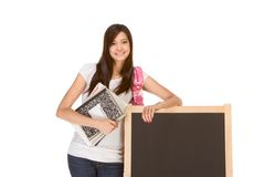Asian student with notebooks by chalk board. Friendly Asian High school girl student standing in jeans with backpack and holding spiral notebooks and composition Royalty Free Stock Photo
