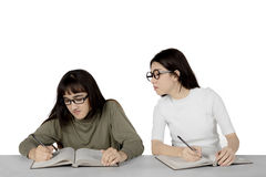 Asian student peeping to her classmate. Image of young Asian student peeping to the textbook of her classmate during exam, isolated on white background stock photography