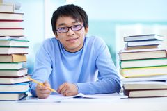 Asian student. Portrait of successful Asian student sitting at workplace Royalty Free Stock Images