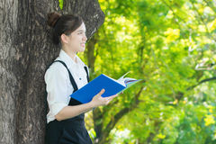 Asian student reading blue book, against green of summer park. Stock Photo