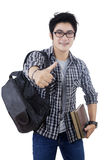 Asian student showing thumb up on studio. Portrait of a young Asian student carrying a backpack and books while showing thumb up in the studio Royalty Free Stock Photography