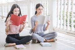 Asian student sitting outside school building reading book. Two asian girls reading book together. Education concept Royalty Free Stock Images
