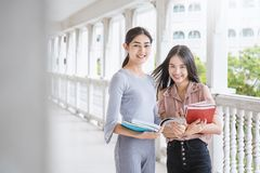 Two asian girls reading book together. Education concept Stock Photography