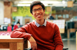 Asian student sitting at the table. Young cheerful asian student sitting at the table Stock Photography