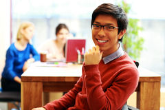 Asian student sitting at the table. Young happy asian student sitting at the table Royalty Free Stock Image