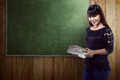 Asian student standing in front of blackboard background Stock Images