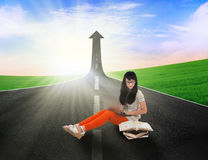 Asian student study on road with up arrow sign Stock Photo