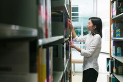 Asian student taking book out of shelf in library. Stock Photo