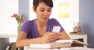 Asian student texting classmate on smartphone Royalty Free Stock Images