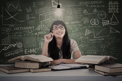 Asian student thinking of solution in class. Asian student thinking under lit bulb in classroom Royalty Free Stock Photos