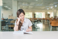 Asian student in uniform reading book at classroom Royalty Free Stock Photos