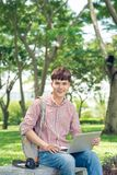 Asian student using laptop sitting in park.  Royalty Free Stock Images