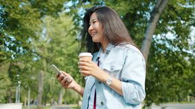 Asian student walking in park using smart phone drinking to go coffee smiling. Asian girl student is walking outdoors in park using smart phone drinking to go stock footage