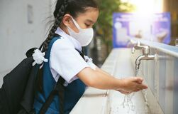 Asian student  washing hands at the outdoor wash basin in the school. Preventing Contagious diseases, Plague. Kids health,