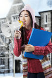 Asian student in winter clothes shouting with megaphone Stock Photos