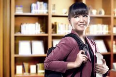 Asian student woman with backpack carrying book standing and look back in the university library. Back to School concept stock image