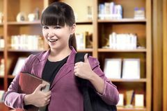 Asian student woman with backpack carrying book standing in the university library. Back to School concept stock photography