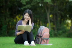 Asian  student. Asian woman college student on campus. She reading book in park Royalty Free Stock Photos