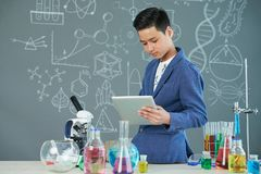 Asian Student Working on Laboratory Report. Portrait shot of handsome Asian student sitting on edge of desk and using modern digital tablet while finishing Stock Photography