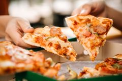 Asian students eating eating the pizza together. In breaking time early next study class having fun and enjoy party, Italian food slice with cheese delicious at Royalty Free Stock Photos