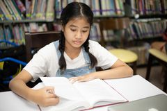 Asian students reading books in the library. royalty free stock image
